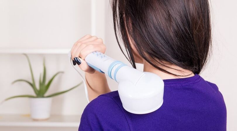 woman using handheld back massager